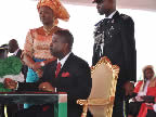 Akwa Ibom State Deputy Governor, His Excellency Obong Nsima Ekere, signs the oath register after taking the oath of office administered by the Chief Judge of Akwa Ibom State, Justice Idongesit Ntemisua, while his wife watches, at the Uyo Stadium on 29th May, 2011